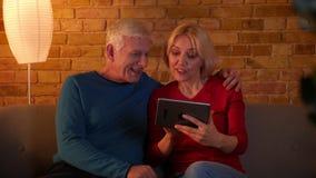 Βλαστός κινηματογραφήσεων σε πρώτο πλάνο του ανώτερου ευτυχούς Ιστού ξεφυλλίσματος ζευγών στην ταμπλέτα που χαμογελά χαρωπά να κα απόθεμα βίντεο