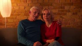 Βλαστός κινηματογραφήσεων σε πρώτο πλάνο του ανώτερου ευτυχούς ζεύγους που προσέχει μια ταινία TV χαρωπά να στηριχτεί στον καναπέ φιλμ μικρού μήκους