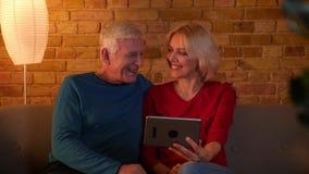 Βλαστός κινηματογραφήσεων σε πρώτο πλάνο του ανώτερου ευτυχούς ζεύγους που έχει μια τηλεοπτική κλήση στη συνεδρίαση ταμπλετών στο απόθεμα βίντεο