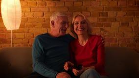 Βλαστός κινηματογραφήσεων σε πρώτο πλάνο του ανώτερου ευτυχούς ζεύγους που προσέχει τη TV χαρωπά να καθίσει στον καναπέ στο εσωτε απόθεμα βίντεο