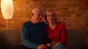 Βλαστός κινηματογραφήσεων σε πρώτο πλάνο του ανώτερου ευτυχούς ζεύγους που προσέχει μια ταινία TV χαρωπά να καθίσει στον καναπέ σ απόθεμα βίντεο