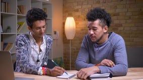 Βλαστός κινηματογραφήσεων σε πρώτο πλάνο του αφροαμερικάνου και των ινδικών ανδρών σπουδαστών που μαθαίνουν από κοινού Δύο φίλοι  απόθεμα βίντεο