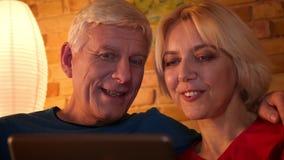 Βλαστός κινηματογραφήσεων σε πρώτο πλάνο του ηλικίας ευτυχούς ζεύγους που κοιτάζει βιαστικά το δίκτυο στη συνεδρίαση ταμπλετών στ φιλμ μικρού μήκους