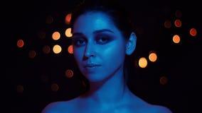 Βλαστός κινηματογραφήσεων σε πρώτο πλάνο του νέου αρκετά καυκάσιου θηλυκού με το μπλε φως νέου και bokeh του υποβάθρου που εξετάζ απόθεμα βίντεο