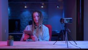 Βλαστός κινηματογραφήσεων σε πρώτο πλάνο του νέου ελκυστικού θηλυκού blogger με τη ροή dreadlocks ζωντανή χρησιμοποιώντας την ταμ φιλμ μικρού μήκους