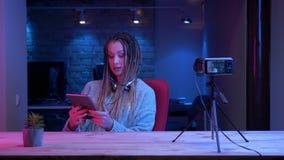 Βλαστός κινηματογραφήσεων σε πρώτο πλάνο του νέου ελκυστικού θηλυκού blogger με τα dreadlocks στη ροή ακουστικών ζωντανή χρησιμοπ απόθεμα βίντεο