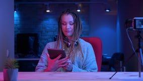 Βλαστός κινηματογραφήσεων σε πρώτο πλάνο του νέου ελκυστικού θηλυκού blogger στη ροή ακουστικών ζωντανή χρησιμοποιώντας την ταμπλ απόθεμα βίντεο