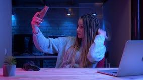 Βλαστός κινηματογραφήσεων σε πρώτο πλάνο του νέου ελκυστικού θηλυκού blogger με τη ροή dreadlocks ζωντανή στο τηλέφωνο που χρησιμ απόθεμα βίντεο