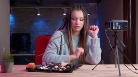 Βλαστός κινηματογραφήσεων σε πρώτο πλάνο του νέου ελκυστικού θηλυκού blogger με τη ροή dreadlocks ζωντανή και τη συζήτηση των προ απόθεμα βίντεο