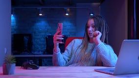 Βλαστός κινηματογραφήσεων σε πρώτο πλάνο του νέου ελκυστικού θηλυκού blogger με τη ροή dreadlocks ζωντανή στο κινητό τηλέφωνο με  απόθεμα βίντεο
