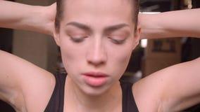 Βλαστός κινηματογραφήσεων σε πρώτο πλάνο του νέου ελκυστικού θηλυκού ταλαντεμένος Τύπου αθλητών που εξετάζει τη κάμερα στη γυμνασ απόθεμα βίντεο