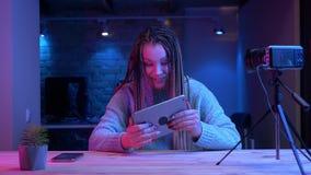 Βλαστός κινηματογραφήσεων σε πρώτο πλάνο του νέου ελκυστικού θηλυκού blogger με τα dreadlocks που στη ροή ταμπλετών ζωντανή με το απόθεμα βίντεο