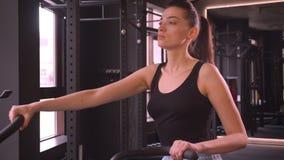 Βλαστός κινηματογραφήσεων σε πρώτο πλάνο του νέου ελκυστικού υγιούς θηλυκού αθλητών με το ponytail που επιλύει στο orbitrek που π απόθεμα βίντεο
