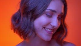 Βλαστός κινηματογραφήσεων σε πρώτο πλάνο του νέου ελκυστικού καυκάσιου θηλυκού που χαμογελά χαρωπά να εξετάσει τη κάμερα με το κό απόθεμα βίντεο