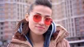 Βλαστός κινηματογραφήσεων σε πρώτο πλάνο του νέου ελκυστικού καθιερώνοντος τη μόδα καυκάσιου κοριτσιού στα κόκκινα γυαλιά ηλίου μ απόθεμα βίντεο