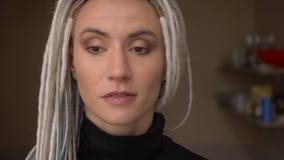 Βλαστός κινηματογραφήσεων σε πρώτο πλάνο του νέου ελκυστικού καυκάσιου θηλυκού hipster με τα ξανθά dreadlocks που εξετάζει ευθέος απόθεμα βίντεο