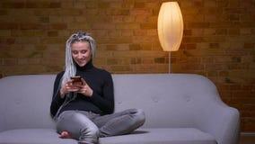 Βλαστός κινηματογραφήσεων σε πρώτο πλάνο του νέου ελκυστικού καυκάσιου θηλυκού hipster με τα ξανθά dreadlocks που στην τηλεφωνική απόθεμα βίντεο