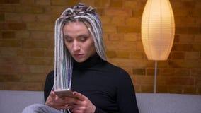 Βλαστός κινηματογραφήσεων σε πρώτο πλάνο του νέου ελκυστικού καυκάσιου θηλυκού hipster με τα ξανθά dreadlocks που χρησιμοποιούν τ φιλμ μικρού μήκους