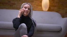 Βλαστός κινηματογραφήσεων σε πρώτο πλάνο του νέου ελκυστικού καυκάσιου θηλυκού με τα ξανθά dreadlocks που καλεί το τηλέφωνο που χ φιλμ μικρού μήκους