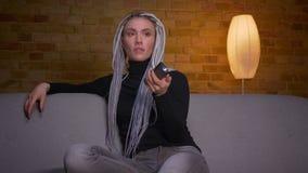 Βλαστός κινηματογραφήσεων σε πρώτο πλάνο του νέου ελκυστικού καυκάσιου θηλυκού hipster που προσέχει μια κωμωδία στη συνεδρίαση TV φιλμ μικρού μήκους
