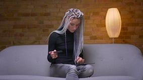 Βλαστός κινηματογραφήσεων σε πρώτο πλάνο του νέου ελκυστικού καυκάσιου θηλυκού hipster με τα dreadlocks που ψωνίζει on-line στην  απόθεμα βίντεο