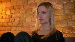 Βλαστός κινηματογραφήσεων σε πρώτο πλάνο του νέου ευαίσθητου θηλυκού που προσέχει έναν λυπημένο κινηματογράφο στη TV που είναι με απόθεμα βίντεο