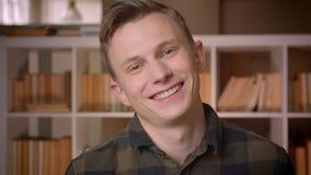 Βλαστός κινηματογραφήσεων σε πρώτο πλάνο του νέου εύθυμου ελκυστικού καυκάσιου άνδρα σπουδαστή που χαμογελά ευτυχώς να εξετάσει τ φιλμ μικρού μήκους