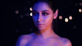 Βλαστός κινηματογραφήσεων σε πρώτο πλάνο του νέου ζαλίζοντας καυκάσιου θηλυκού με το πορφυρές φως νέου και bokeh την τοποθέτηση υ απόθεμα βίντεο