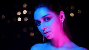 Βλαστός κινηματογραφήσεων σε πρώτο πλάνο του νέου ζαλίζοντας καυκάσιου θηλυκού με το φως νέου και bokeh την τοποθέτηση υποβάθρου  απόθεμα βίντεο