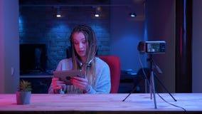 Βλαστός κινηματογραφήσεων σε πρώτο πλάνο του νέου θηλυκού blogger με τα dreadlocks στη ροή ακουστικών ζωντανή χρησιμοποιώντας την φιλμ μικρού μήκους