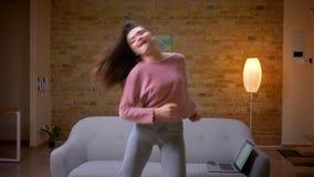 Βλαστός κινηματογραφήσεων σε πρώτο πλάνο του νέου όμορφου γέλιου χορού brunette καυκάσιου θηλυκού και κατοχή της διασκέδασης σε έ φιλμ μικρού μήκους