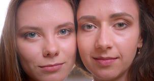Βλαστός κινηματογραφήσεων σε πρώτο πλάνο του νέου όμορφου λεσβιακού ζεύγους που χαμογελά ευτυχώς να εξετάσει τη κάμερα από κοινού φιλμ μικρού μήκους