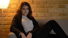 Βλαστός κινηματογραφήσεων σε πρώτο πλάνο του χαλάρωσης του νέου αρκετά καυκάσιου θηλυκού και της TV προσοχής καθμένος στον καναπέ στοκ εικόνες
