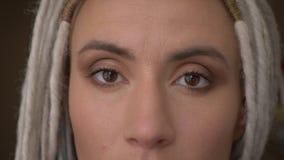 Βλαστός ματιών κινηματογραφήσεων σε πρώτο πλάνο του νέου ελκυστικού καυκάσιου θηλυκού hipster με τα ξανθά dreadlocks που εξετάζει φιλμ μικρού μήκους