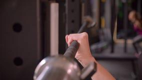 Βλαστός πλάγιας όψης κινηματογραφήσεων σε πρώτο πλάνο των νέων ελκυστικών θηλυκών χεριών αθλητών που παίρνουν έτοιμων να ανυψώσει απόθεμα βίντεο