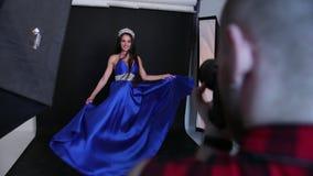Βλαστός φωτογραφιών στο στούντιο, ένα κορίτσι brunette σε ένα μπλε φόρεμα, με το βαθύ neckline απόθεμα βίντεο