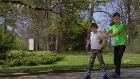 Βοήθεια αδελφών ο μικρότερος αδερφός του για να μάθει να οδηγά στα σαλάχια κυλίνδρων απόθεμα βίντεο
