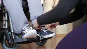 Βοήθεια ενός με ειδικές ανάγκες νεαρού άνδρα στην αναπηρική καρέκλα απόθεμα βίντεο