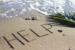 Βοήθεια - σημάδι στην άμμο σε ένα υπόβαθρο του κλάδου θάλασσας και φοινικών στοκ φωτογραφίες με δικαίωμα ελεύθερης χρήσης