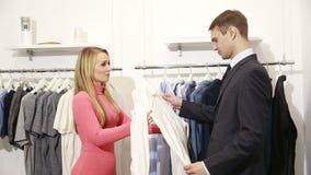 Βοηθητικό παρουσιάζοντας πουκάμισο καταστημάτων ανδρών στη γυναίκα στη λεωφόρο άτομο σε ένα επιχειρησιακό κοστούμι που φαίνεται π απόθεμα βίντεο