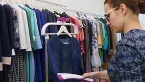 Βοηθητικό φόρεμα σιδερώματος καταστημάτων με το ατμόπλοιο ενδυμάτων στο κατάστημα ενδυμάτων απόθεμα βίντεο