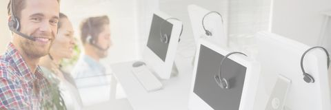 Βοηθοί εξυπηρέτησης πελατών με τις κάσκες με το φωτεινό υπόβαθρο γραφείων στοκ φωτογραφίες