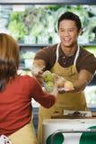 Βοηθοί πωλήσεων που δίνουν τα πακέτα των μήλων στοκ εικόνες