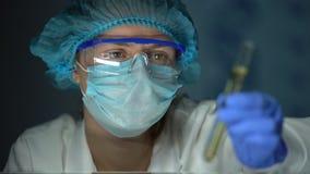 Βοηθός εργαστηρίων που εξετάζει το σωλήνα με το διαφανές κίτρινο υγρό, δοκιμή βιολογικών καυσίμων φιλμ μικρού μήκους