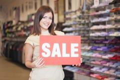 Βοηθός καταστημάτων που κρατά την ειδοποίηση «πώλησης» Στοκ εικόνες με δικαίωμα ελεύθερης χρήσης