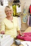 Βοηθός πωλήσεων θηλυκών στο κατάστημα ιματισμού στοκ φωτογραφίες