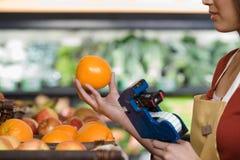 Βοηθός πωλήσεων που διατιμά ένα πορτοκάλι στοκ φωτογραφίες με δικαίωμα ελεύθερης χρήσης