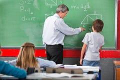 Βοηθώντας μαθητής δασκάλων λύνοντας Στοκ Εικόνα