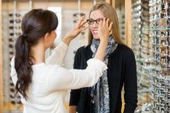 Βοηθώντας πελάτης πωλητριών στη φθορά των γυαλιών Στοκ Φωτογραφίες