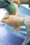 Βοηθώντας χειρούργος νοσοκόμων με το αποστειρωμένο γάντι λατέξ Στοκ φωτογραφία με δικαίωμα ελεύθερης χρήσης